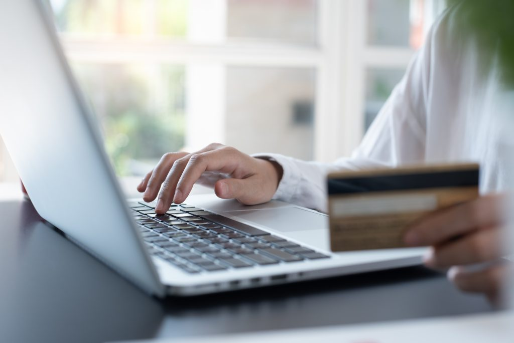 Man sitting at laptop with credit card in hand making purchase online
